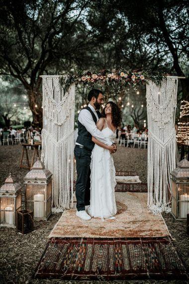 Bride in Max Mara wedding dress with groom under macrame arch