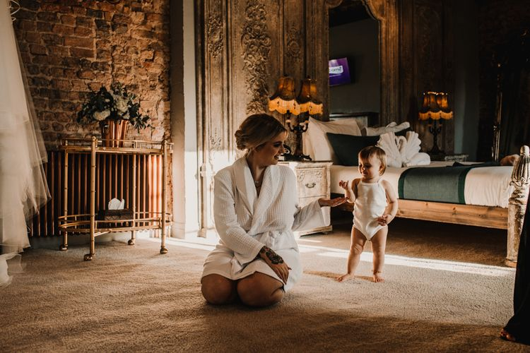 Wedding Morning Bridal Preparations with Bride in Getting Ready Robe Kneeling Down Playing With Her Daughter