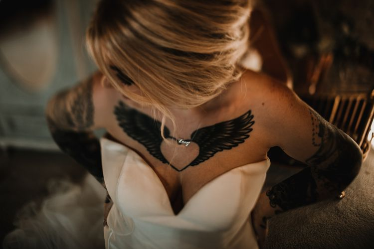 Tattooed Bride in Sweetheart Neckline Wedding Dress Showing Off Her Heart and Wings Ink