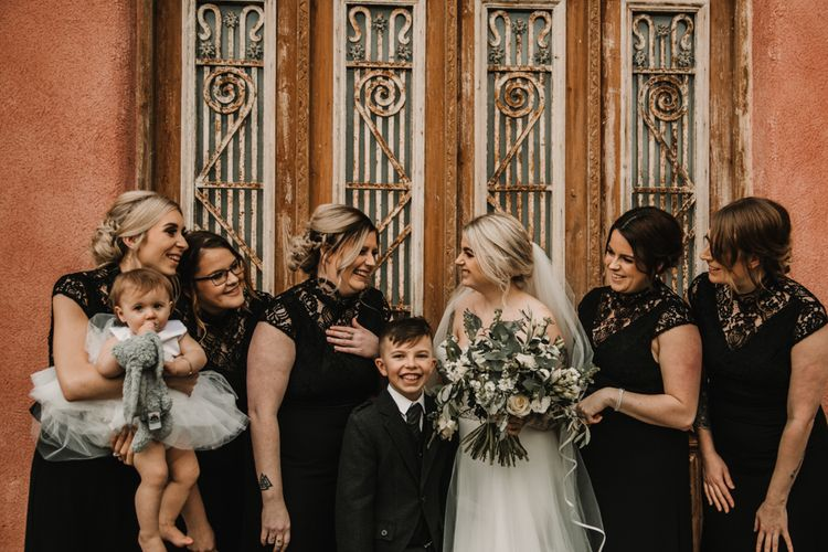 Bridal Party Portrait with Bride in Mermaid Wedding Dress and Bridesmaids in Black Lace Dresses