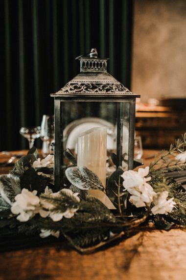 Lantern Centrepiece Surrounded by White and Green Wedding Flowers