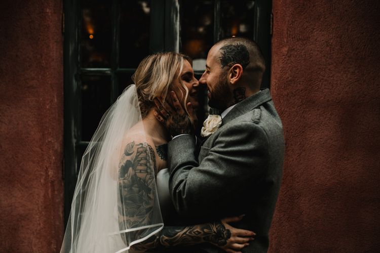 Tattooed Bride with Sweetheart Wedding Dress and Groom in Highland Wear Embracing Her Face