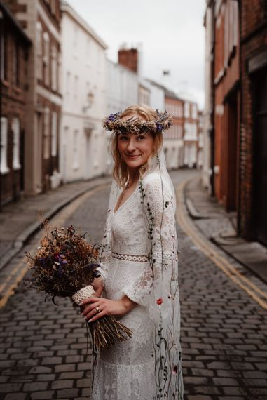 Boho bride with lace wedding dress, flower crown and embroidered veil
