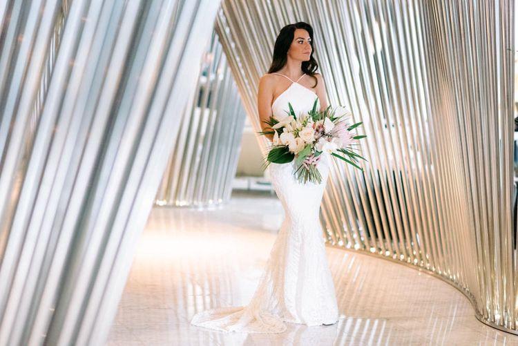 Striking bride wearing Vagbond Bridal with King Protrea Wedding Bouquet