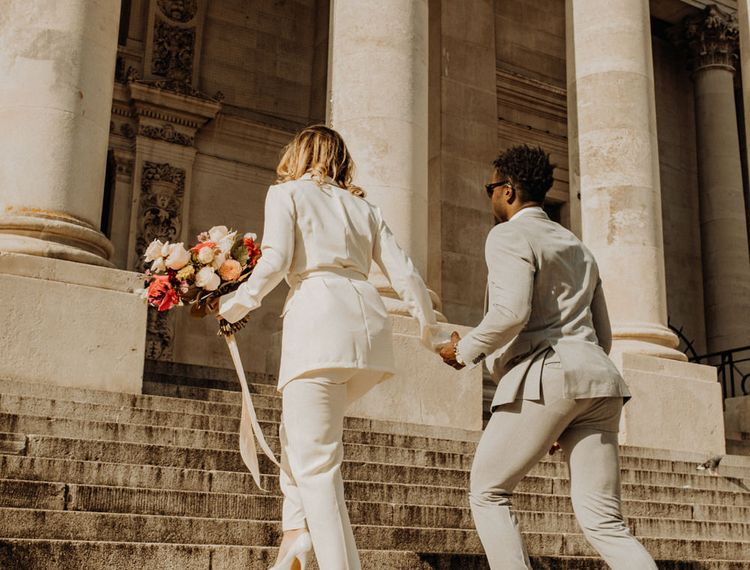 Stylish bride and groom walking up the steps of Portsmouth Guidhall