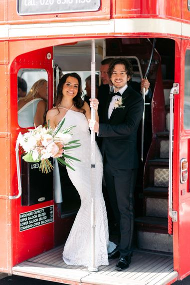 Bride and groom on red London wedding bus