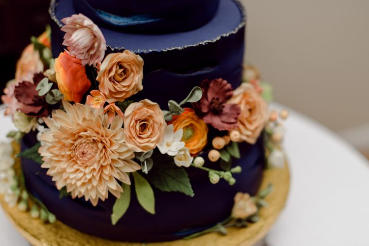 Navy blue wedding cake with floral decor