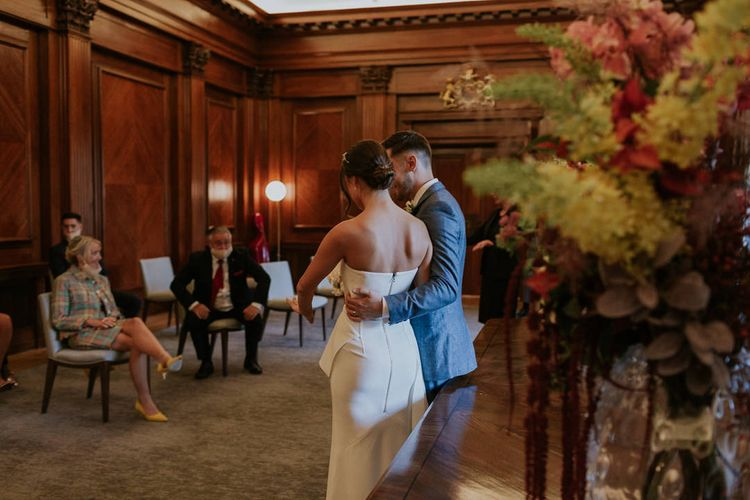 Groom embracing his bride at town hall micro wedding