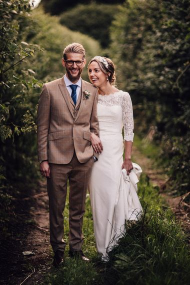 Bride in lace wedding dress and groom in brown check suit at rustic wedding