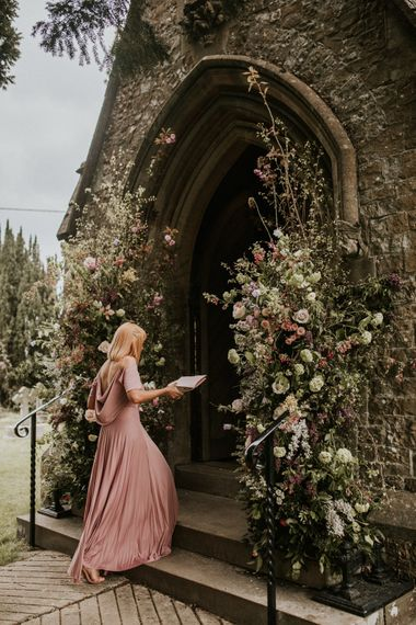 Bridesmaid in dusky pink dress entering the church