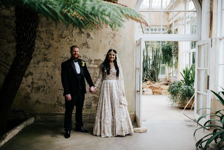 Bride in ivory and gold embellished wedding dress and groom in tuxedo at Syon Park conservatory reception