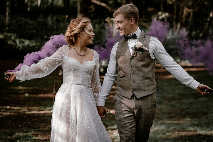 Bride and groom waving smoke bombs in Sherwood Glade woodland wedding