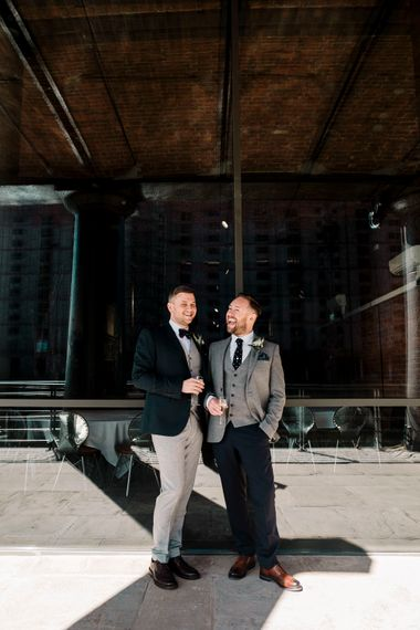 Grooms in light grey and green suits at city wedding