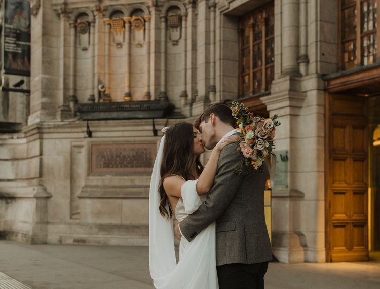 Bride and groom kissing outside their Holy Trinity Brompton Church wedding