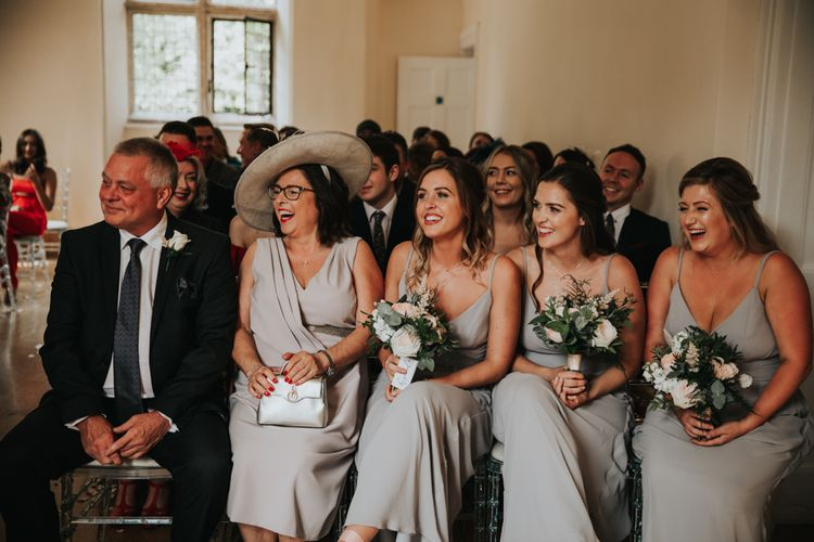 Mother of the bride and bridesmaids laughing and smiling during the wedding ceremony