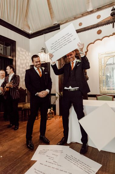 Groom holds up lyrics for guests to sing