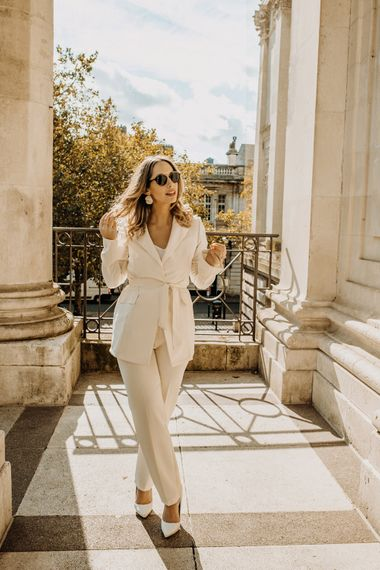 Bride in high street trouser suit and sunglasses at city elopement