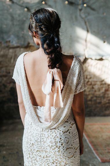 新娘穿着白色亮片连衣裙,低V背,新娘辫子用缎带系着