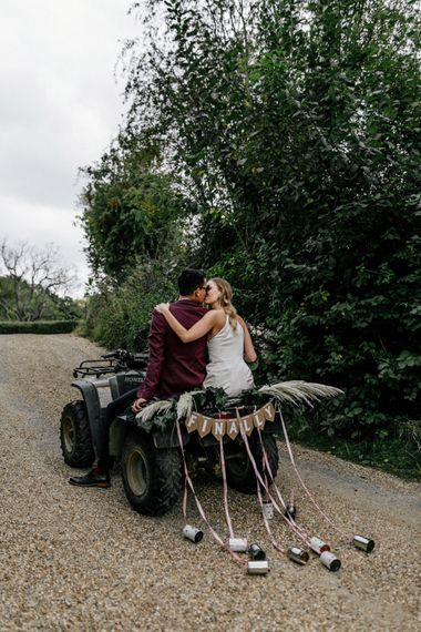 Bride and groom riding a quad bike with tin cans trailing