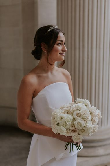 Bride in Roland Mouret wedding dress holding an all white wedding bouquet