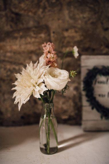 wedding flower stems in bottles decorating the church