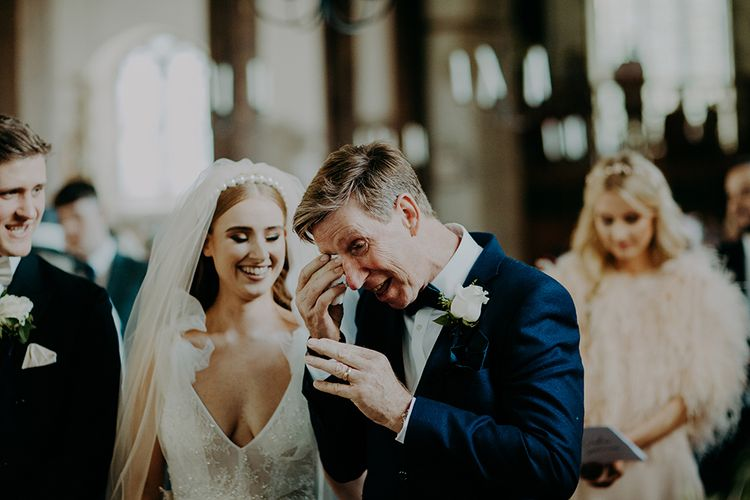Emotional father of the bride during church wedding