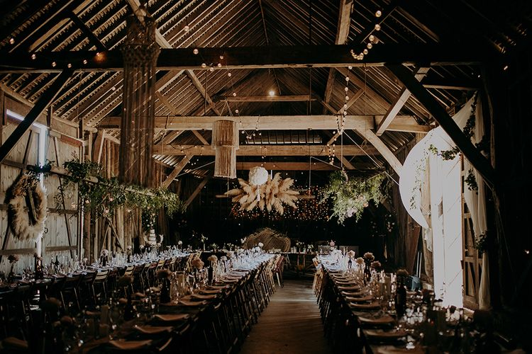 Barn wedding reception filled with rustic wedding decor, foliage and dried flowers