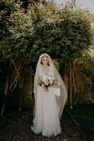 Stylish bride in Inbal Dror wedding dress and cathedral length veil