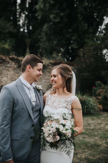 Groom in grey suit and bride in fitted wedding dress with lace illusion bodice