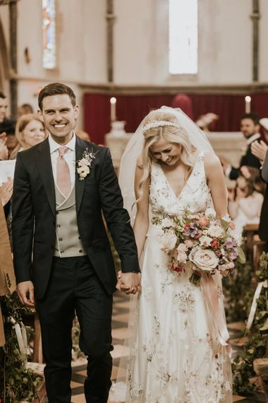 Confetti moment with bride in a floral embroidered wedding dress