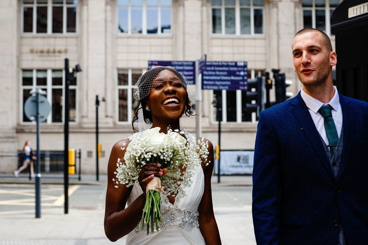Bride in birdcage veil smiling holding her rose and gypsophila bouquet