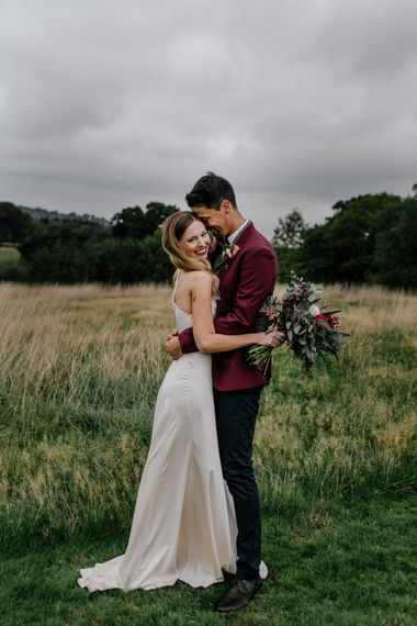Bride and groom embracing in a field at High Billinghurst Farm micro wedding
