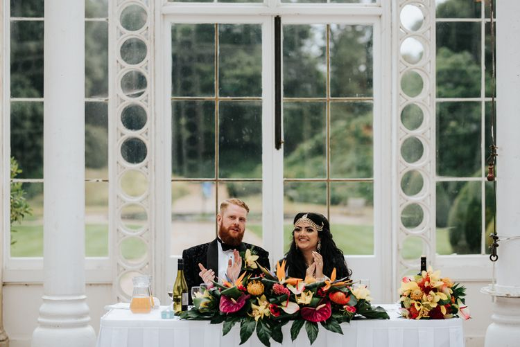 Bride and groom sitting at their wedding reception sweetheart table