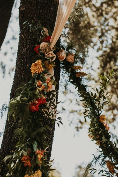 Orange and yellow wedding flowers with foliage decorating the trees at Andalusia wedding