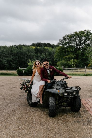 Stylish bride and groom riding a quad bike