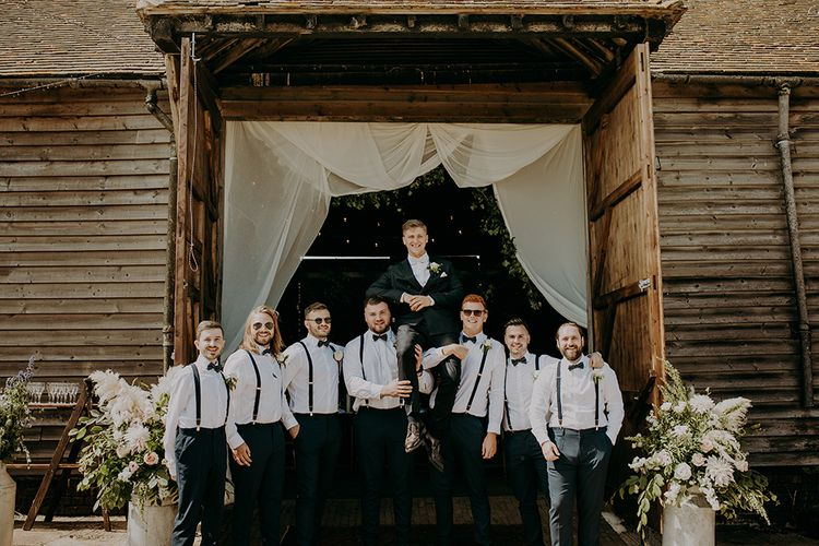 Groomsmen in white shirts and braces