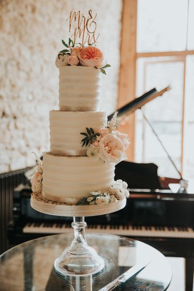 Classic buttercream wedding cake decorated with flowers