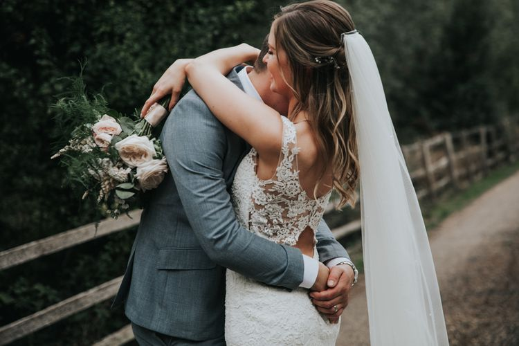 Groom embracing his bride in a lace back wedding dress