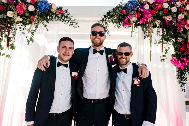 Groomsmen in tuxedos and bow ties