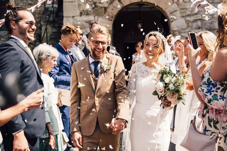 Church confetti moment with bride in Sassi Holford wedding dress and groom in brown check suit