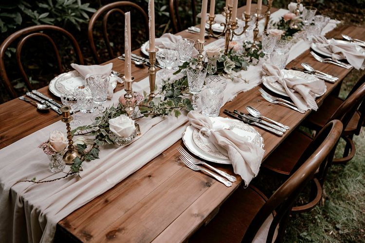 Intimate woodland wedding table with charger plates and candlesticks