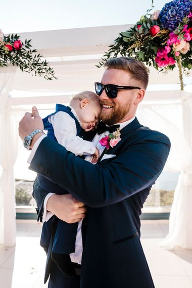 Groom in tuxedo and sunglasses holding a baby