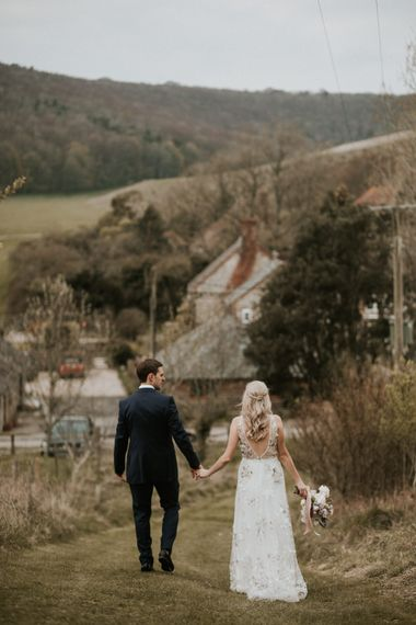 Bride in floral embroidered wedding dress and groom in navy suit at Upwaltham Barn wedding