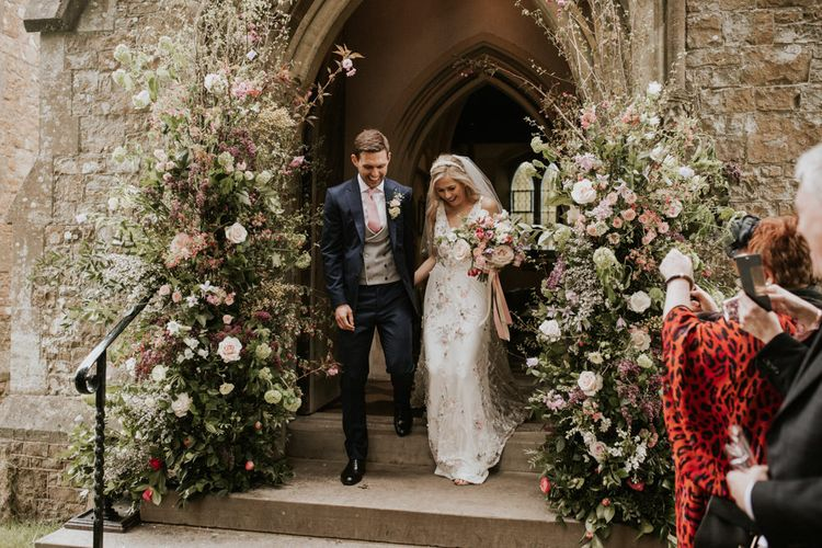 Bride and groom exiting the church with flower arrangements