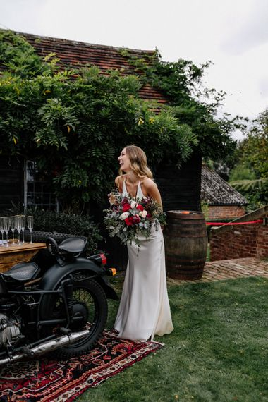 Bride in satin wedding dress standing next to a motorcycle prosecco bar