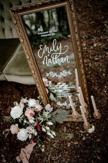 Vintage mirror wedding welcome sign with flower and candlestick decor