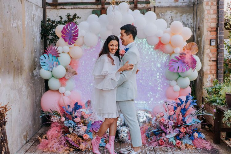 Bride and groom standing in front of a balloon installation