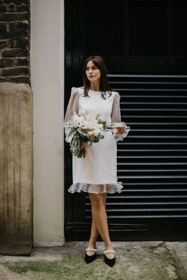 Micro wedding dress by Story Of My Dress with sheer long sleeves and frill edges