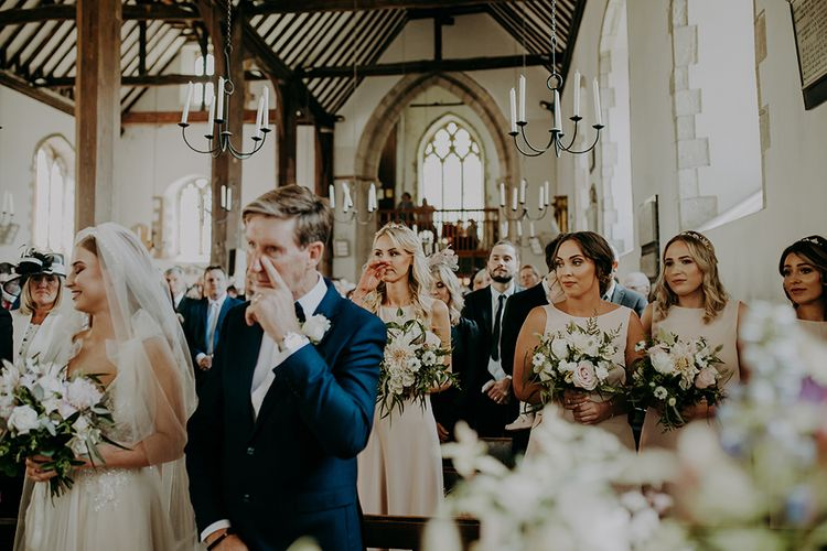 Emotional father of the bride and bridesmaid at church wedding ceremony