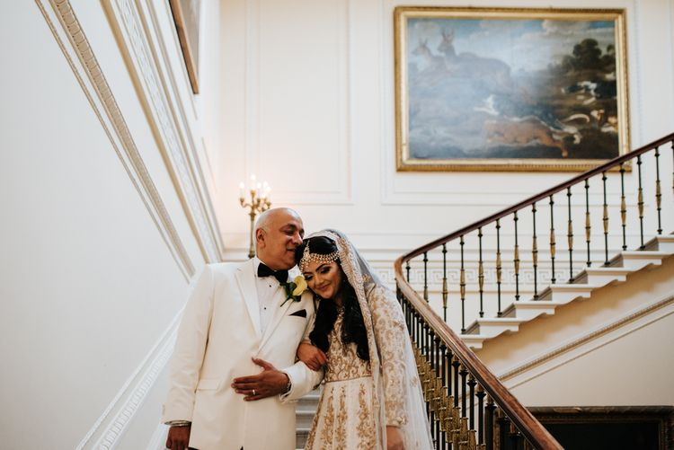 Father of the bride in white tuxedo kissing his daughter
